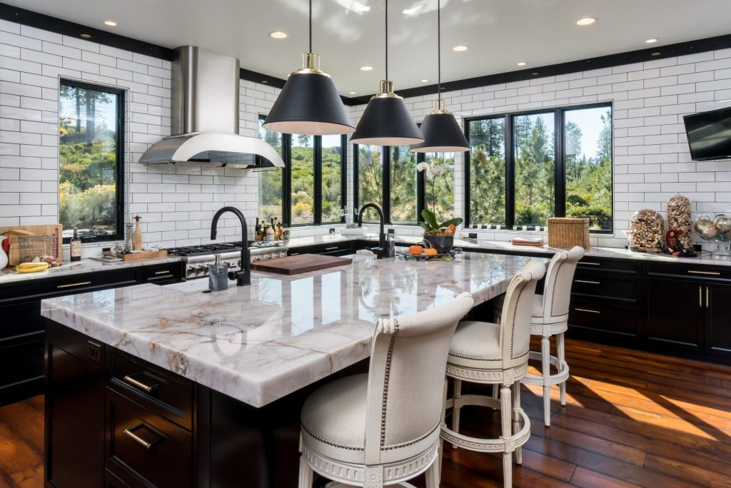 Custom stone slab countertop in a kitchen with tile and wood floors.